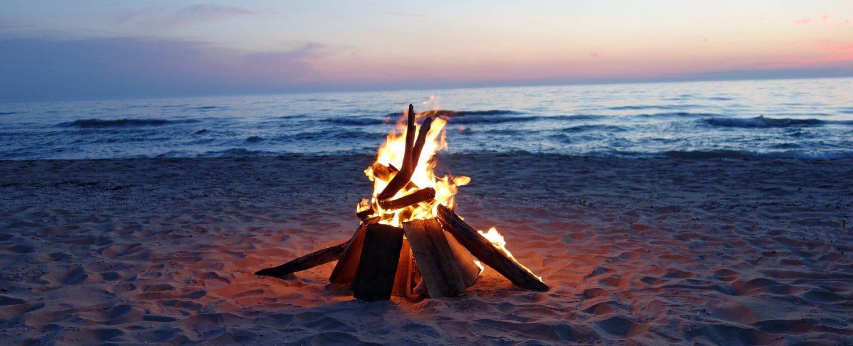 Beautiful campfire by the lake at dusk.