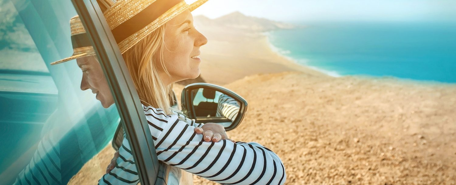 Happiness young woman sitting in her white car and look on the beautifull ocean coastline view. Freedom, Travell, Journej, Trip concept.