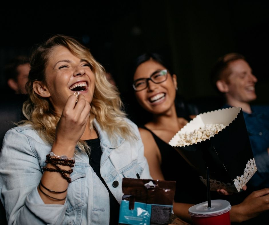 People laughing and eating popcorn at a move theater.