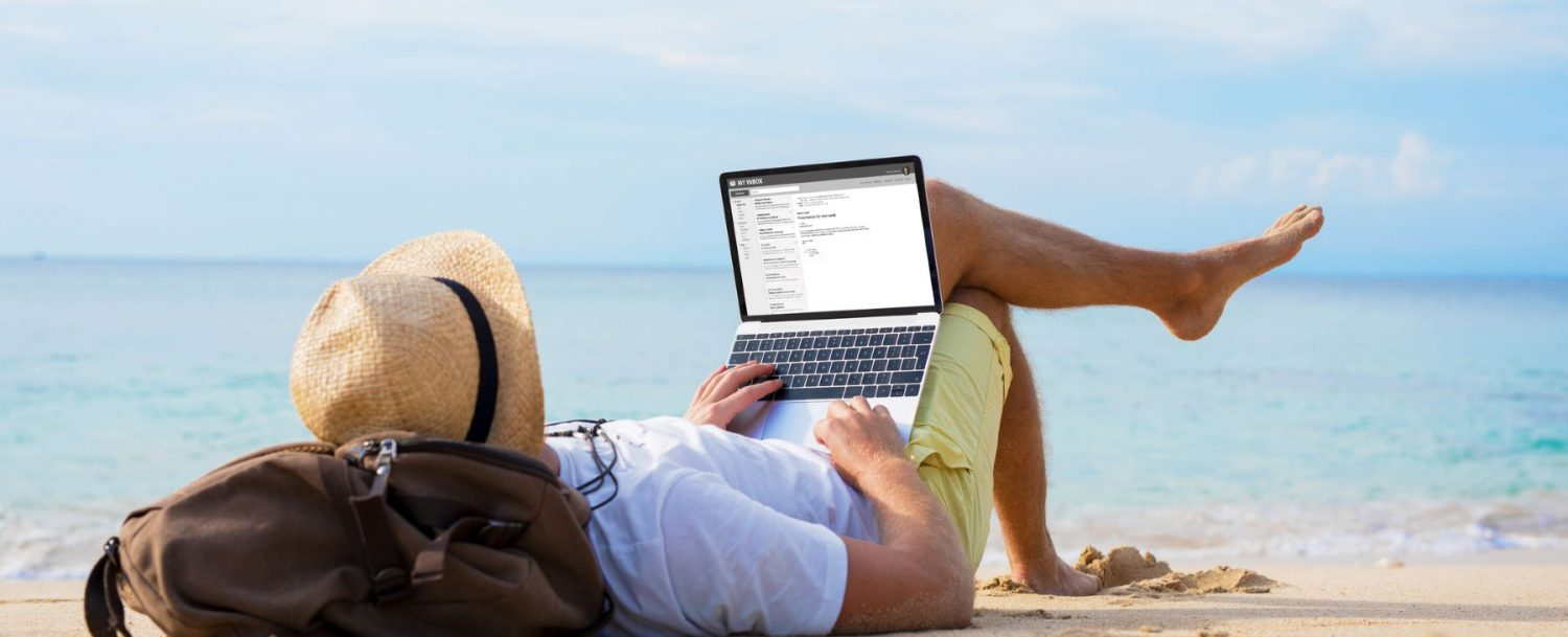 Person working on a laptop from the beach.