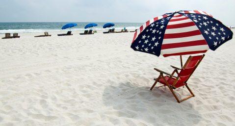 Beach chair with American flag umbrella on the beach.