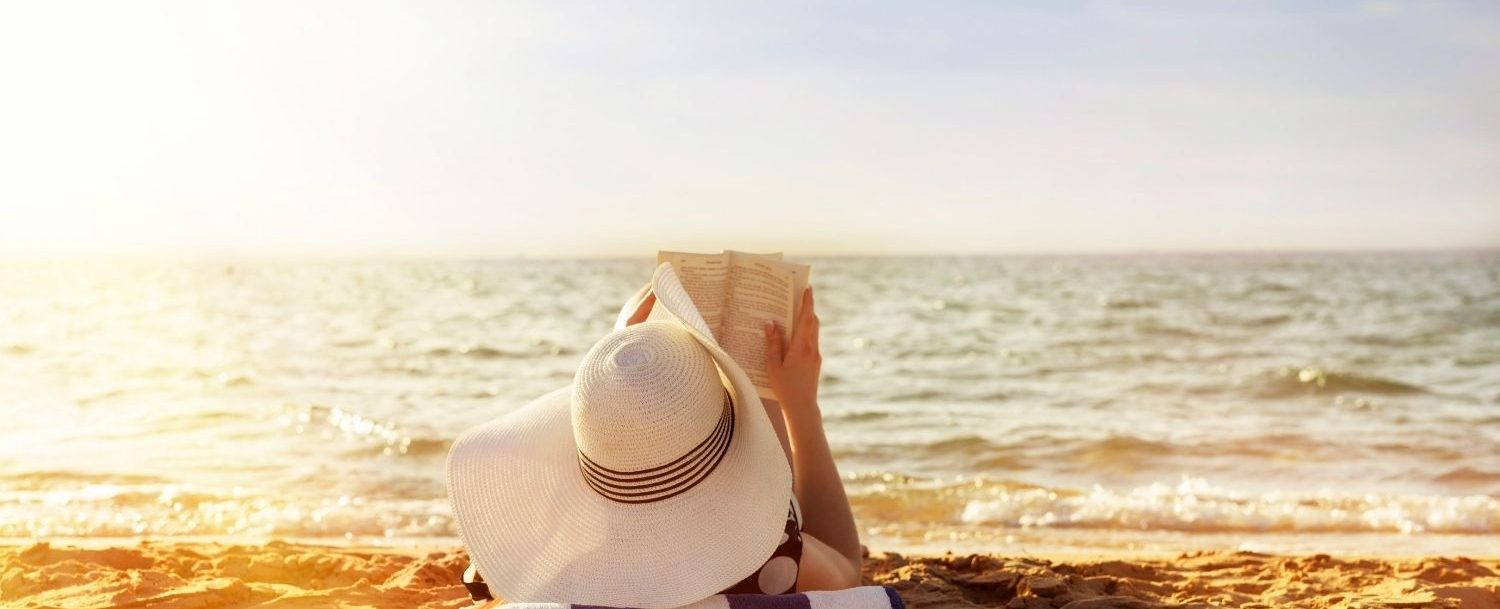 Woman reading book on the beach.