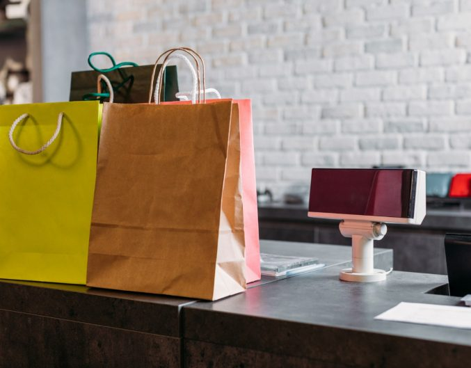 shopping bags standing on cash register in shopping mall, boutique shopping concept