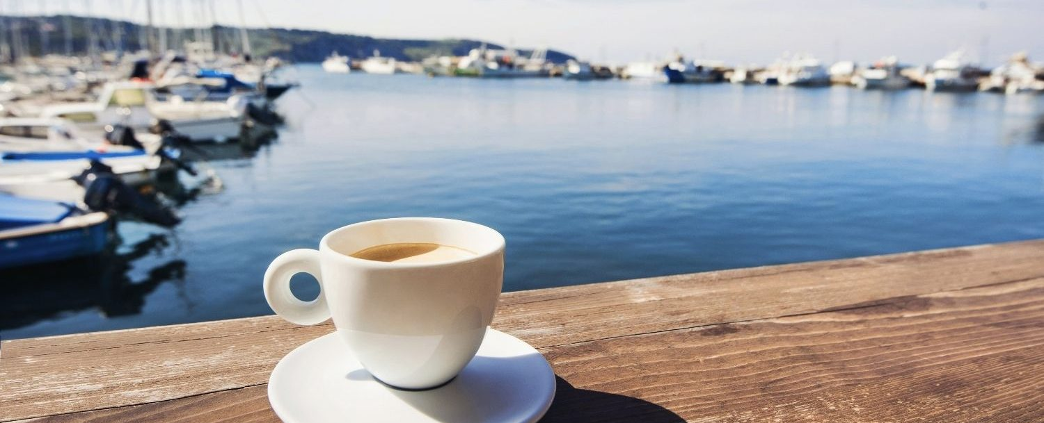 Coffee cup on the dock by the ocean.