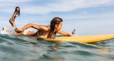 Two women surfing