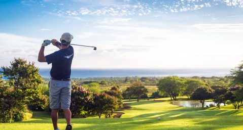 Man golfing with ocean views